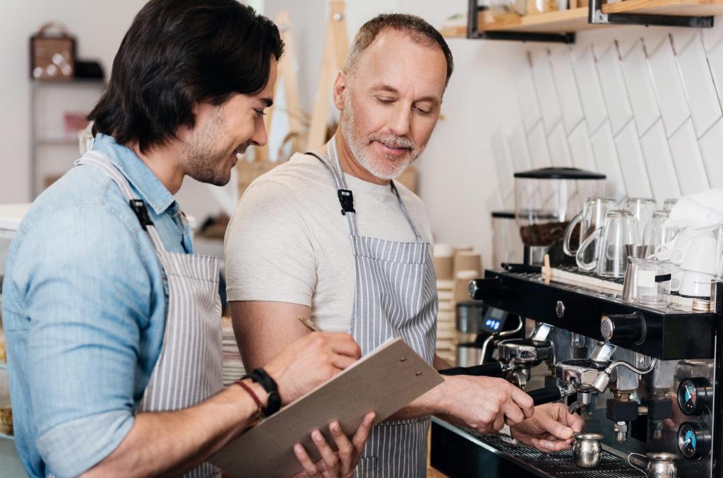 Generationenübergreifende Zusammenarbeit: älterer und jüngerer Mann gemeinsam an einer Gastro-Kafeemaschine
